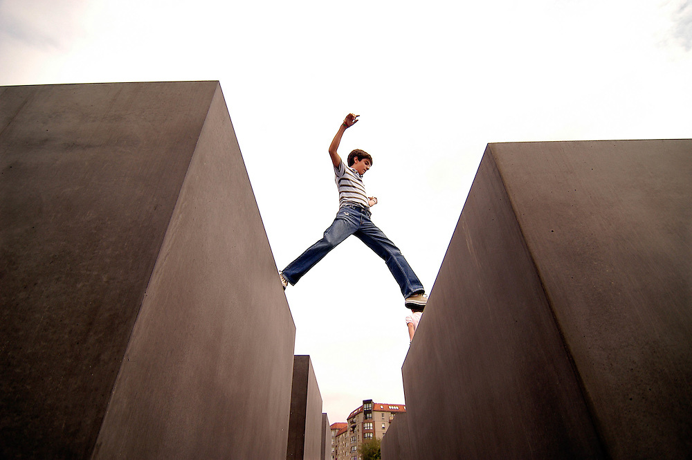 A young boy jumps between pedestals in Berlin's Memorial to the Murdered Jews of Europe.