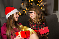 Sisters with Christmas presents looking at each other on sofa