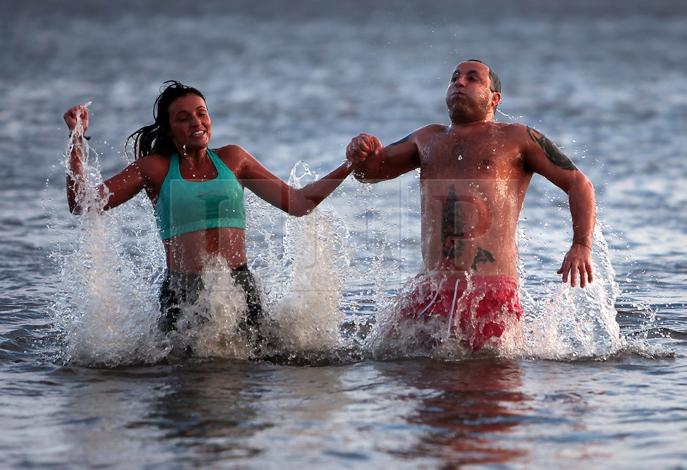 Licensed to London News Pictures. 01/01/2013, Whitley Bay, North Tyneside, UK. Carly Williams with dad Dave Cass-Williams join hundreds of swimmers braving the freezing North Sea as they take to the water in the annual Panama Swimming Club New Year Swim at Whitley Bay. Photo credit: Adrian Don/LNP