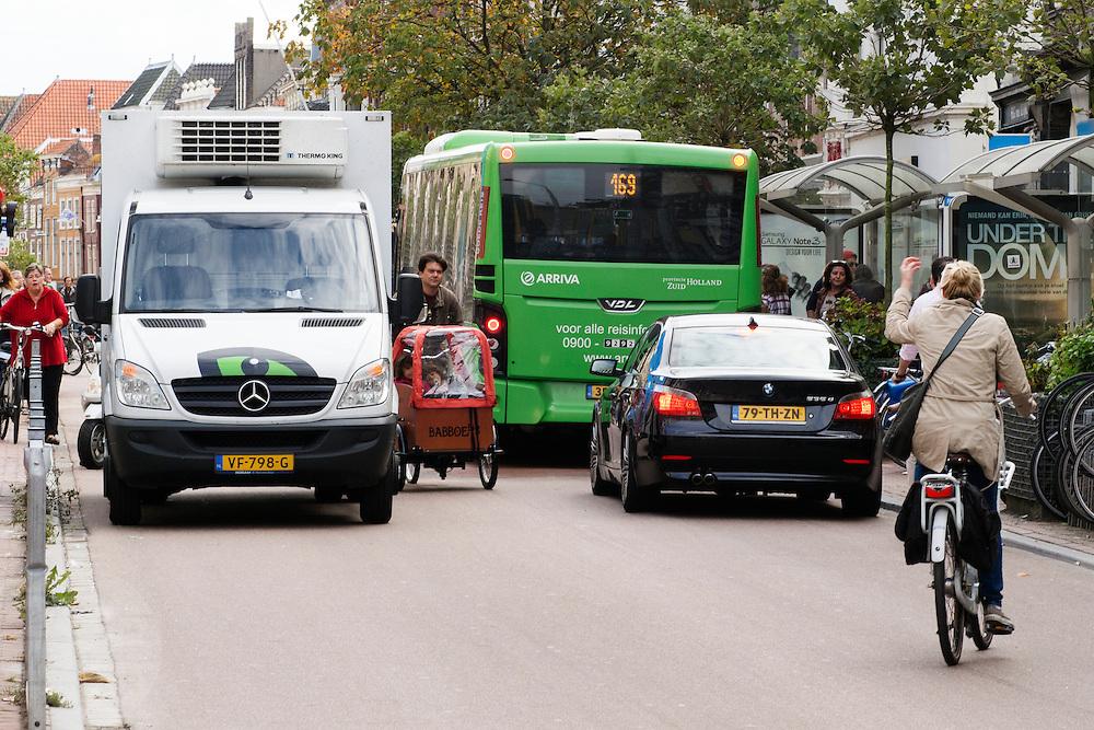 Een man met een bakfiets moet zich tussen een bus en een vrachtwagen wurmen. In Leiden delen fietsers de rijstrook met bussen en bevoorradingsverkeer.<br /> <br /> Cyclists in Leiden share their lane with buses and small trucks.