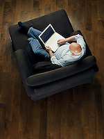 Middle-aged man sitting on sofa using laptop view from above