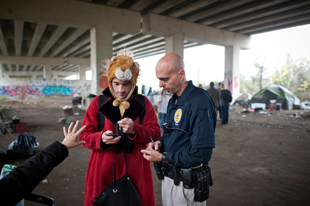 Savannah Metro Police Department's Homeless Liaison Officer Tom Gentner, right,  gathers contact information from a young couple who are living in homeless  camp eight south under the ramps of the Truman Parkway, Monday, Dec. 9, 2013, in Savannah, Ga. Since September of 2013 the Savannah police department gave Gentner the task of documenting over three hundred homeless people living near the historic downtown area.  (AP Photo/Stephen B. Morton)