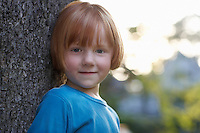 Portrait of girl (5-6) leaning against tree