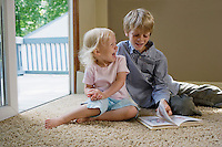 Young boy (5-6) with sister (1-2) sitting on carpet with book laughing