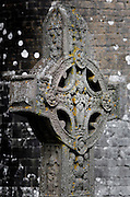 Detail of The Cross of the Scripture (replica), 10th century, against the O' Rourke's tower, Clonmacnoise, County Offaly, Ireland. Clonmacnoise was founded by St Ciaran, with the help of Diarmait Ui Cerbaill, Ireland's first Christian King. The site presents the largest collection of Early Christian graveslabs in Western Europe. Picture by Manuel Cohen