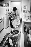 Single mother, Shameka, sorts through laundry after a full day at work.