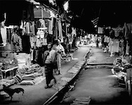 Karen woman makes her way along covered street in Mae La refugee camp resembles a souq or bazar in South Asia or the Middle East.  Merchants are mainly Indo - Burmese refugee who have fled the fighting in Kayan (Karen) State in Burma (Myanmar).