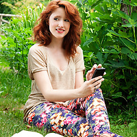 Smiling young woman using a phone and relaxing at park