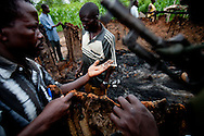 "Patroling ""arrow boys"" inspect a house burnt down by the LRA outside of Tambura. The ""arrow boys"" are a self defence force that hs sprung up in Western Equatoria to defend against the LRA."