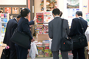 Japanese businessmen browsing at a magazine stand