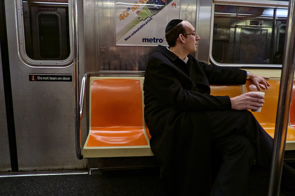 Man in long coat holding coffee cup on subway