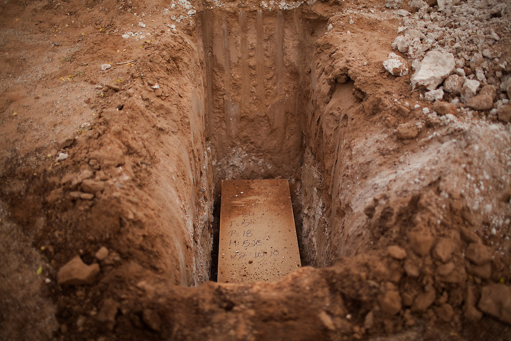 A coffin of an unidentified murder victim waits to be buried at a cemetery in Ciudad Juarez.