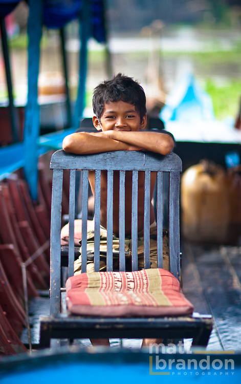 A young Cambodian boy hides behind of wooden chair on his boat.