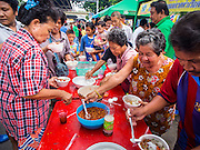 "07 AUGUST 2014 - BANGKOK, THAILAND:   People put chilies and condiments on their noodle soup during a community food distribution program at Pek Leng Keng Mangkorn Khiew Shrine in Bangkok. Thousands of people lined up for food distribution at the Pek Leng Keng Mangkorn Khiew Shrine in the Khlong Toei section of Bangkok Thursday. Khlong Toei is one of the poorest sections of Bangkok. The seventh month of the Chinese Lunar calendar is called ""Ghost Month"" during which ghosts and spirits, including those of the deceased ancestors, come out from the lower realm. It is common for Chinese people to make merit during the month by burning ""hell money"" and presenting food to the ghosts. At Chinese temples in Thailand, it is also customary to give food to the poorer people in the community.      PHOTO BY JACK KURTZ"