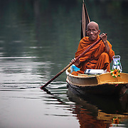 Thai Buddhist monk Luang Pho Malai, 91 years old, is seen Saturday, June 29, 2013, as he paddles his way along a river canal near his pagoda on the outskirts of Bangkok.   For the past 30 years Luang Pho Malai has made his daily round to attend to the faithful in a small wooden boat to collect their offers and dispense blessings.  While many of Bangkok's major canals were filled in and paved over during the building boom of the 1980's klong Thavi Watthana still serves the needs of a impoverished community.