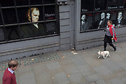 A lady walks her pet dog past the faces and biographies of famous achievers, alumni of Kings College London University on the Strand, on 6th September, in London, England.