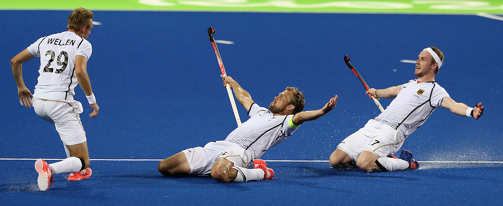 RIO DE JANEIRO, BRAZIL - AUGUST 14:  Moritz Furste, (C) of Germany who scored a late equalising goal celebrates with team mates Christopher Ruhr (R) and Niklas Wellen (L) during the Men's hockey quarter final match between the Germany and New Zealand on Day 9 of the Rio 2016 Olympic Games at the Olympic Hockey Centre on August 14, 2016 in Rio de Janeiro, Brazil.  (Photo by David Rogers/Getty Images)