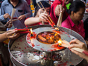 "19 FEBRUARY 2015 - BANGKOK, THAILAND:  People light candles and incense on Chinese New Year at Wat Mangkon Kamalawat in Bangkok. 2015 is the Year of Goat in the Chinese zodiac. The Goat is the eighth sign in Chinese astrology and ""8"" is considered to be a lucky number. It symbolizes wisdom, fortune and prosperity. Ethnic Chinese make up nearly 15% of the Thai population. Chinese New Year (also called Tet or Lunar New Year) is widely celebrated in Thailand, especially in urban areas that have large Chinese populations.   PHOTO BY JACK KURTZ"