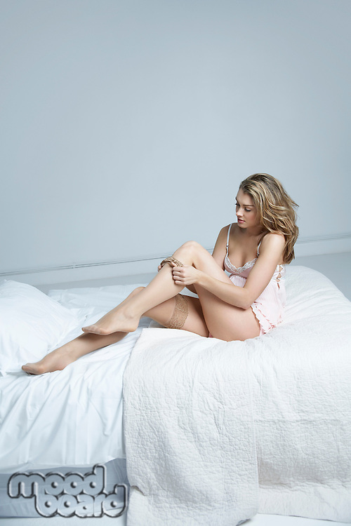 Young woman putting on stockings on bed