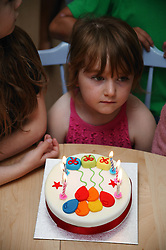 Young girl waiting to blow out candles on her birthday cake,