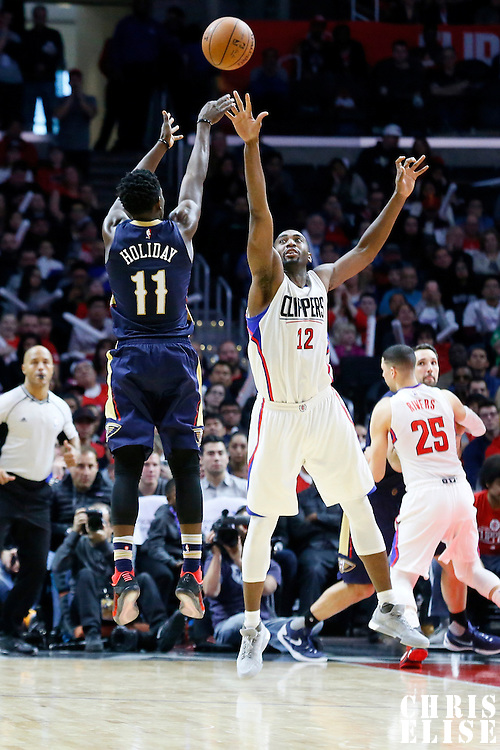 10 January 2016: New Orleans Pelicans guard Jrue Holiday (11) takes a jump shot over Los Angeles Clippers forward Luc Richard Mbah a Moute (12) during the Los Angeles Clippers 114-111 overtime victory over the New Orleans Pelicans, at the Staples Center, Los Angeles, California, USA.