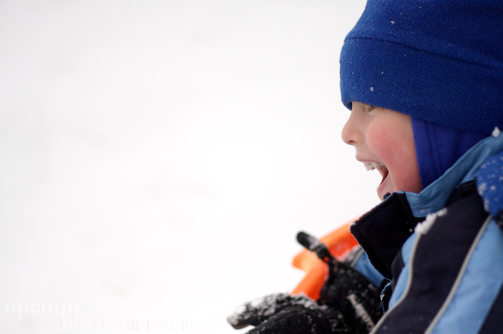 A five-year-old boy laughs in the snow after sledding down a hill, Steamboat Springs, CO.