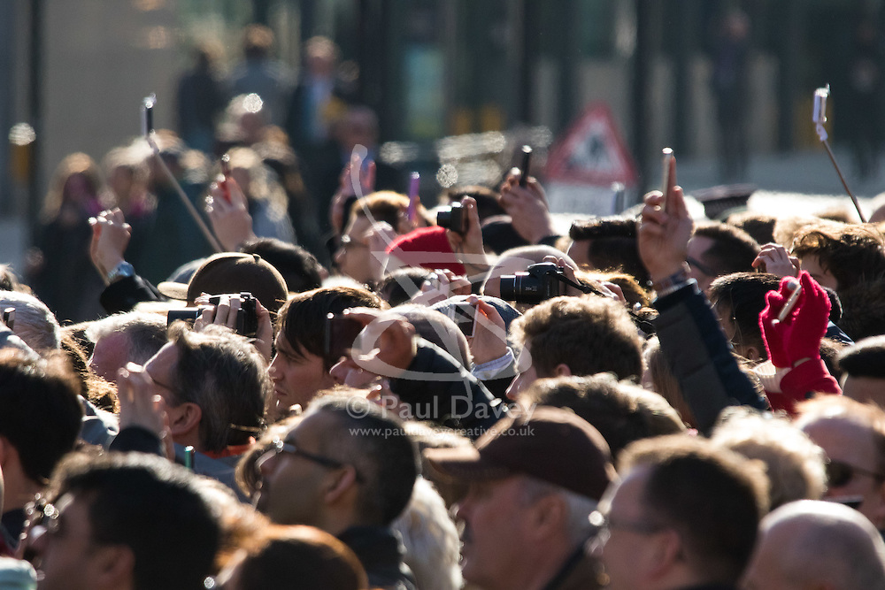 Westminster Abbey, London, March 14th 2016.  Her Majesty The Queen, Head of the Commonwealth, accompanied by The Duke of Edinburgh, The Duke and Duchess of Cambridge and Prince Harry attend the Commonwealth Service at Westminster Abbey on Commonwealth Day. PICTURED: Crowds of bystanders strive to get a picture.