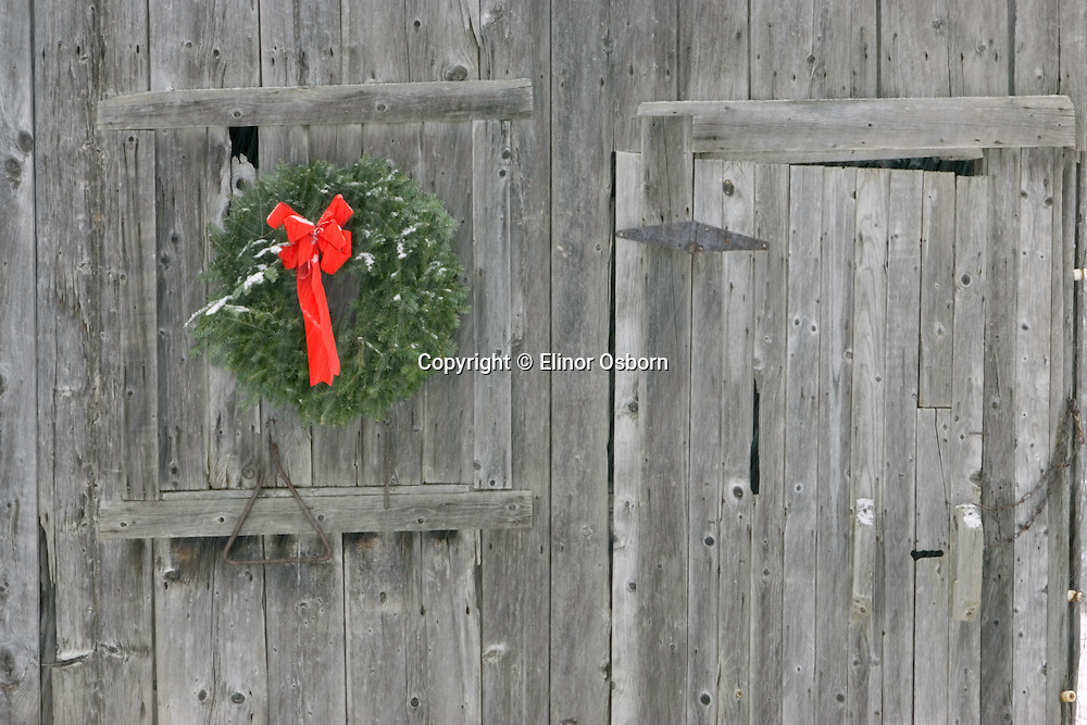 Old Vermont Barn with Christmas wreath and triangle, falling snow