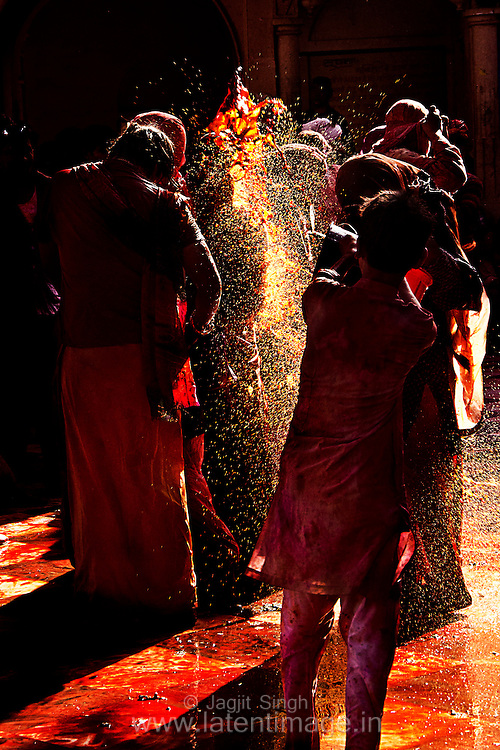 A boy throwing water color on people gather during Holi at Barsana, Mathura. Braj ki Holi