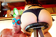 A drunken man leans asleep next to the buttocks of a woman on a bar stool. He has dressed up for a party.