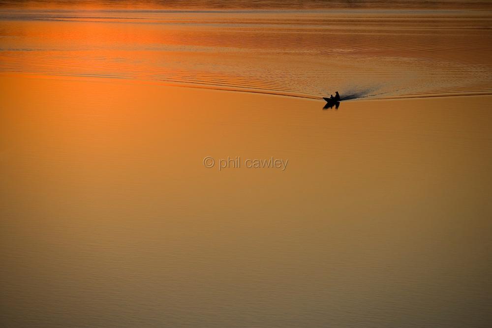 Laos - Luang Prabang, mekong river, silhouette of a small boat