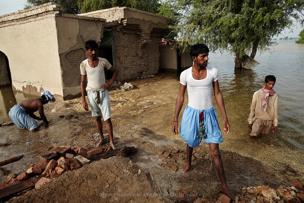 Men examine the damage to their home after floodwater swept through the area near Bubak, Sundh province, Pakistan.
