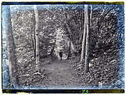 boy with hiking stick in idilic woods hiking path setting 1900s
