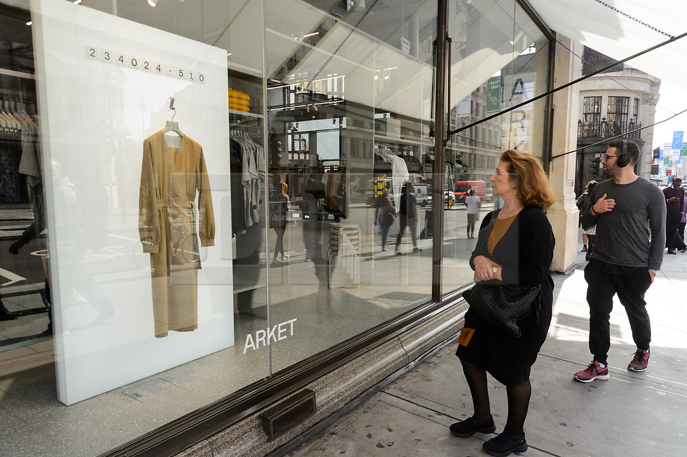 © Licensed to London News Pictures. 25/08/2017. London, UK. A woman and man look at a window display at the opening of H&M group's first ARKET flagship store in Regent Street. ARKET has called itself a modern day market seeing not only clothes, but homeware as well as a small cafe space. Photo credit: Ray Tang/LNP