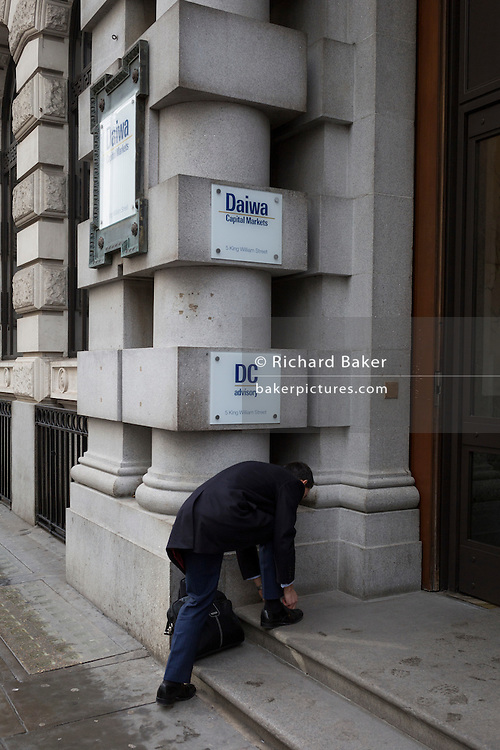 A businessman stops to tie a shoelace in the doorway of banking and financial companies, on 2nd February 2017, in the City of London, England.