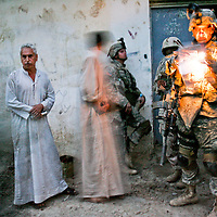 A US soldier with the 2/9 Cavalry, 3rd Brigade, 4th Infantry Division, checks identification cards of a man and his son against a list of names of individuals suspected of sectarian violence in the village of Abu Sayda in Diyala province, northeast of Baghdad. US and Iraqi Army soldiers conducted an overnight sweep through this mainly Shia neighborhood looking for individuals suspected of committing sectarian violence in the area. October 2006.