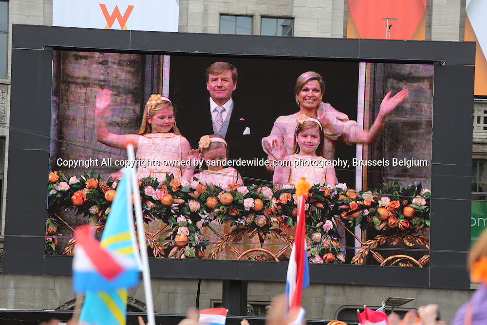 30th April 2013 Amsterdam, Netherlands. Dam Square. Queen Beatrix' abdication takes place, and her son Prince Willem-Alexander will be King of the Netherlands. the new royal family with king Willem queen maxima and kids at the balcony scene seen on a screen at dams square