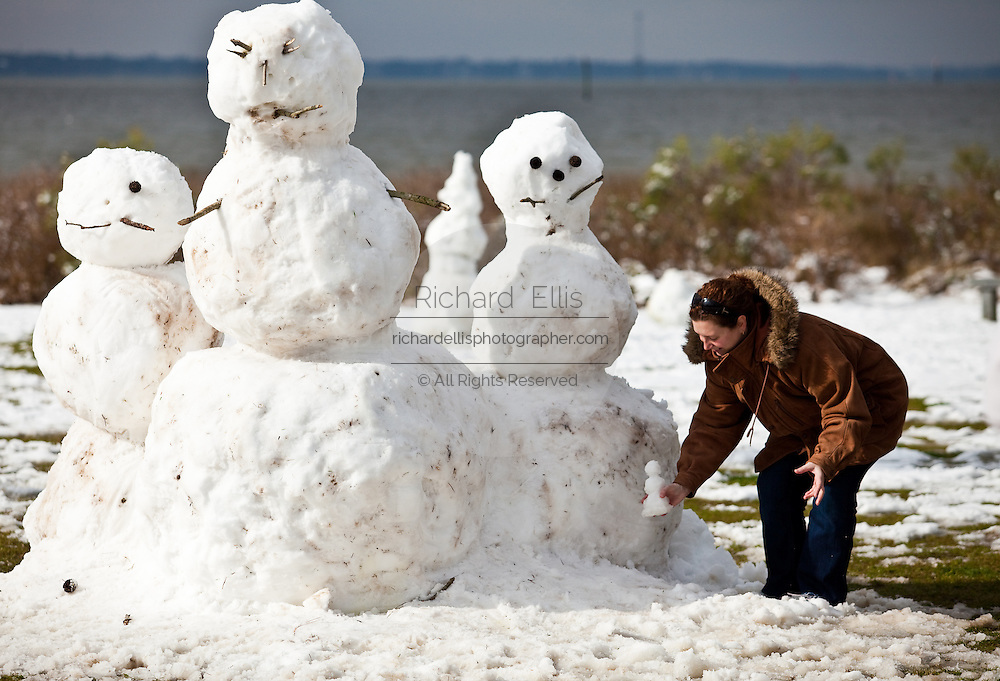 CHARLESTON, SC - February 13: A woman adds a tiny snowman to a snowman family February 13, 2010 during a rare snow storm in Mt Pleasant, SC. About 3-inches of snow fell on the Charleston area, the first significant snow in 20-years.    (Photo Richard Ellis/Getty Images)