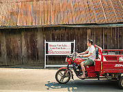 "13 MARCH 2016 - LUANG PRABANG, LAOS: A Lao man rides his tractor past a home for sale in Luang Prabang. The for sale sign being in English indicates who the property is being marketed to. Luang Prabang was named a UNESCO World Heritage Site in 1995. The move saved the city's colonial architecture but the explosion of mass tourism has taken a toll on the city's soul. According to one recent study, a small plot of land that sold for $8,000 three years ago now goes for $120,000. Many longtime residents are selling their homes and moving to small developments around the city. The old homes are then converted to guesthouses, restaurants and spas. The city is famous for the morning ""tak bat,"" or monks' morning alms rounds. Every morning hundreds of Buddhist monks come out before dawn and walk in a silent procession through the city accepting alms from residents. Now, most of the people presenting alms to the monks are tourists, since so many Lao people have moved outside of the city center. About 50,000 people are thought to live in the Luang Prabang area, the city received more than 530,000 tourists in 2014.    PHOTO BY JACK KURTZ"