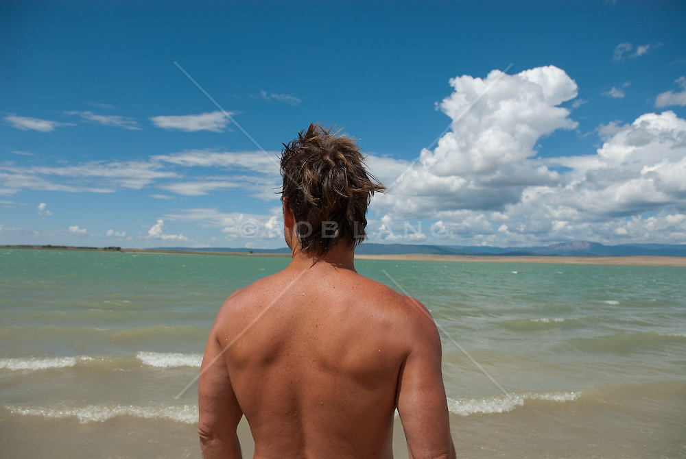 Shirtless man looking out over rough water on a lake