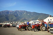 Farmers sit of the back of their tractors whilst discussing prices for their tomatoes.