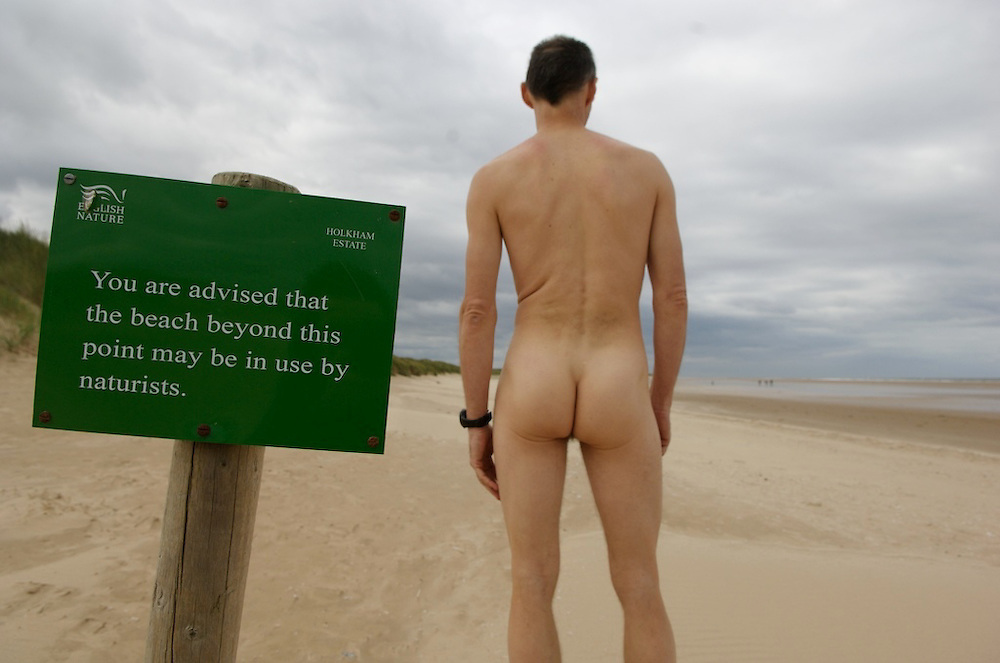 A naturist enjoys a barren beach on England's Norfolk coast.