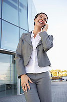 Businesswoman talking on mobile phone in front of office building