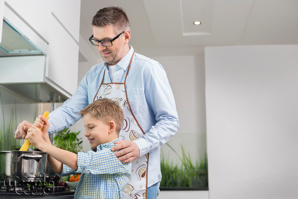 Father and son preparing spaghetti in kitchen