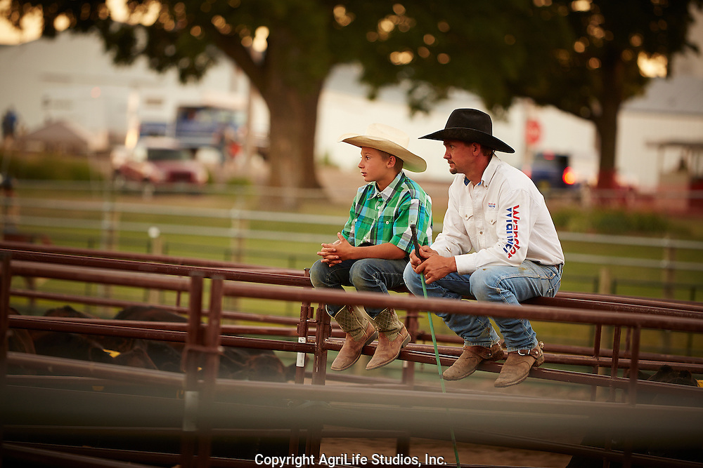 Father and son, watching rodeo, sitting on the fence, midwest county fair