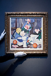 "© Licensed to London News Pictures. 18/11/2013. London, UK. A member of Christie's staff adjusts ""Still life with roses in a blue and white vase"" (est. GB£300,000 - 500,000), painted by Scottish artist John Peploe in the early 1920's, at the press view for a sale of modern British and Irish art at Christie's St James' auction house in London today (18/11/2013). The sale is set to take place on Wednesday the 20th and Thursday the 21st of November 2013. Photo credit: Matt Cetti-Roberts/LNP"