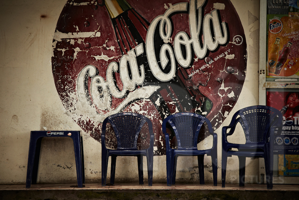 Plastic chairs and a table branded by Pepsi sit in front of a fading Coca Cola sign covering the wall, Vietnam, Southeast Asia