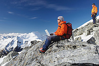 Mountain climber using laptop on mountain peak
