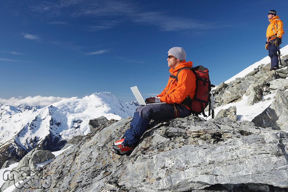 Mountain climber using laptop on mountain peak