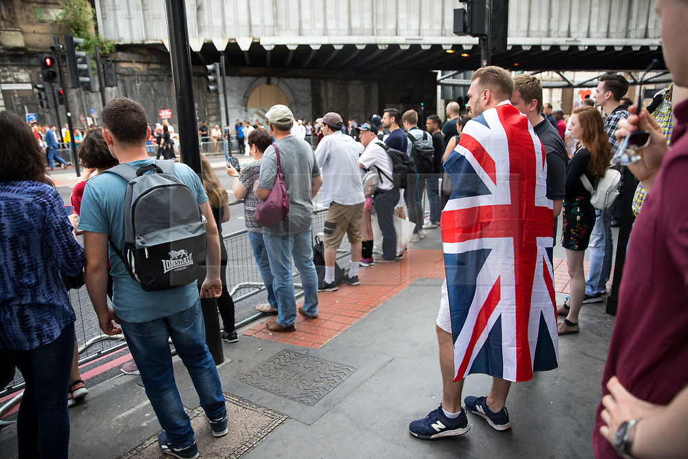 © Licensed to London News Pictures. 03/06/2018. London, UK. A man wearing a Union Jack flag watches on as people mark the anniversary of the London Bridge and Borough Market terror attacks. A series of events have taken place throughout the day, including a service of commemoration at Southwark Cathedral, the planting of an olive tree in the Cathedral grounds, a minute's silence at 4:30pm and the laying of flowers.  Photo credit : Tom Nicholson/LNP